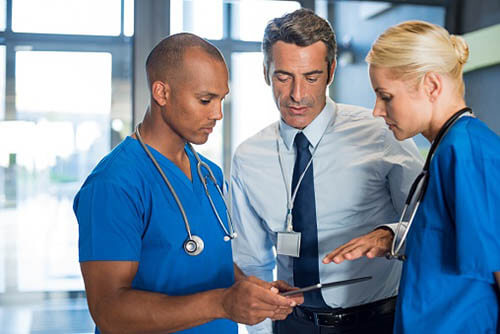 Healthcare workers reviewing the 11 measure included in the 2017 Advancing Care Information Objectives and Measures