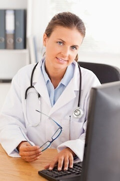 Doctor sitting by a computer